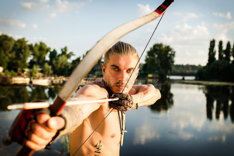 The arrows from the bow river. Male Archer on the banks of the river pulls the arrow royalty free stock images
