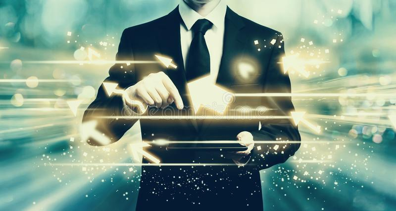 Arrows with man holding a tablet stock image