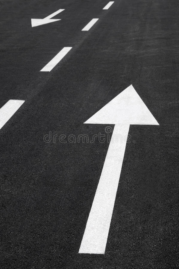 Arrows in oposite ways. Concept with white asphalt arrows royalty free stock photography