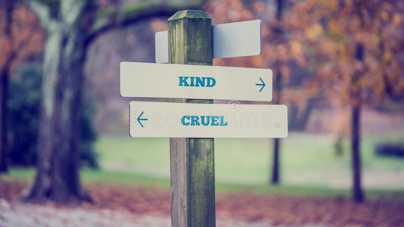 Arrows pointing two opposite directions towards Kind and Cruel. Signpost in a park or forested area with arrows pointing two opposite directions towards Kind and stock photo