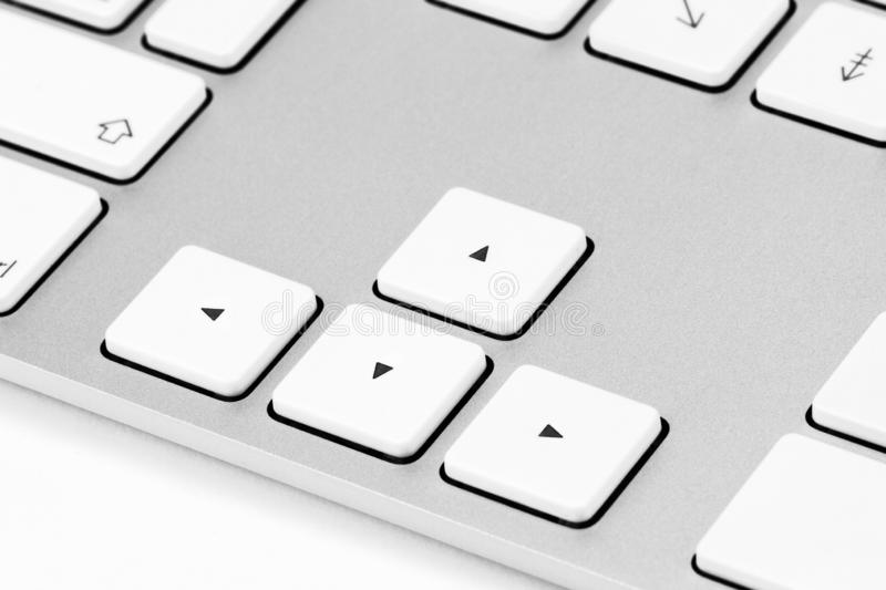 Arrows on a white aluminum keyboard. Elements of a white computer keyboard close up stock photography