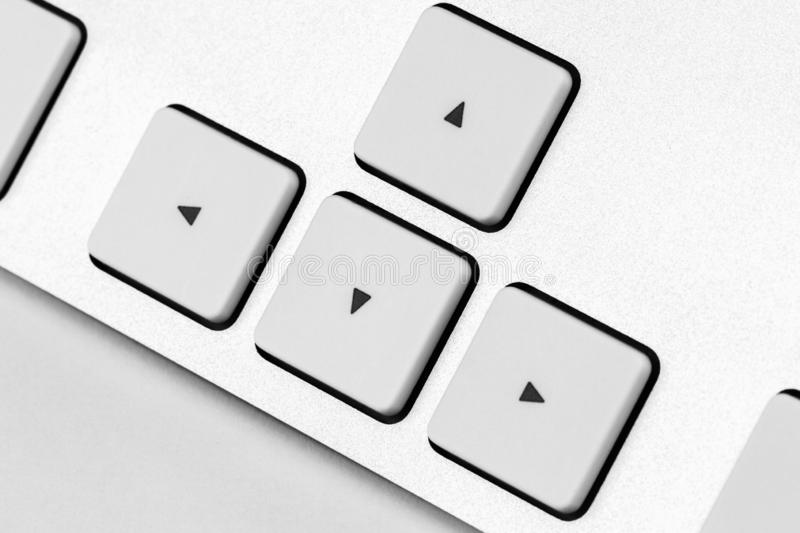 Arrows on a white aluminum keyboard. Elements of a white computer keyboard close up stock photo