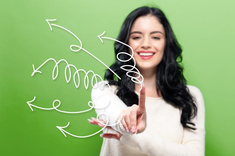 Arrows with young woman. Pointing on a green background stock photo