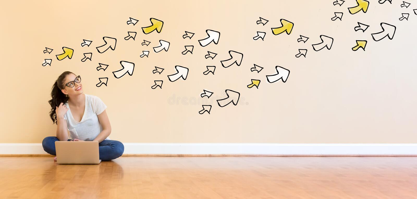 Arrows with young woman using a laptop computer. On floor stock image