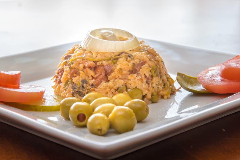 Arroz amarillo tradicional de la cocina cubana con las aceitunas imagenes de archivo