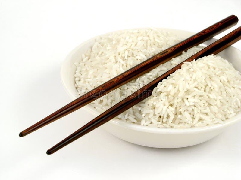Arroz branco de Uncook na bacia com varas da costeleta fotografia de stock