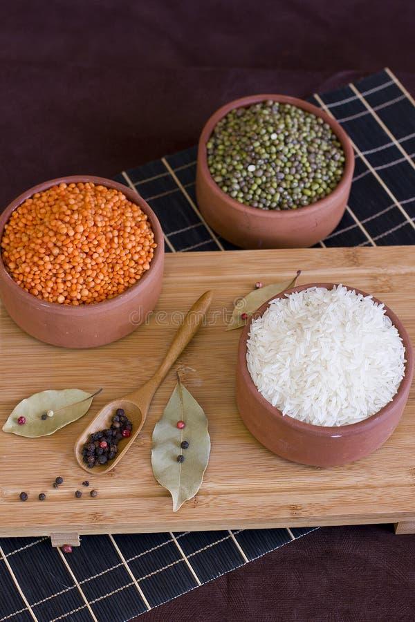 Arroz branco, lentilhas vermelhas e mache das ervilhas verdes na bandeja de madeira baía foto de stock