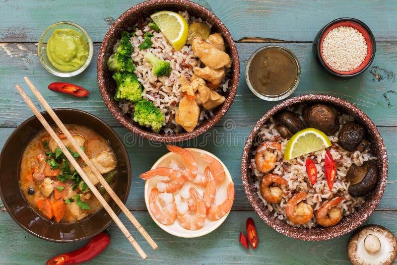 Arroz con las gambas, pollo, setas, bróculi en un fondo rústico desnudo Platos asiáticos Concepto de comida asiática Endecha plan imágenes de archivo libres de regalías