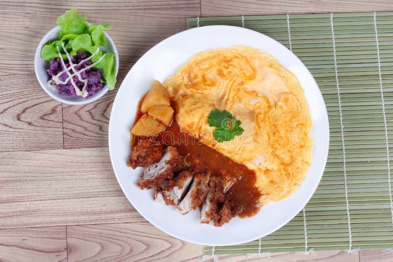 Arroz da omeleta com a galinha fritada no caril amarelo japonês no marrom Vista superior fotografia de stock