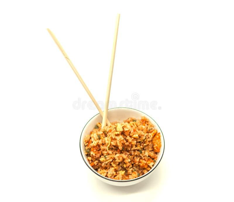 Arroz de Fried Chinese con las verduras y el huevo, en un cuenco en un fondo blanco con los palillos El favorito chino adorna foto de archivo