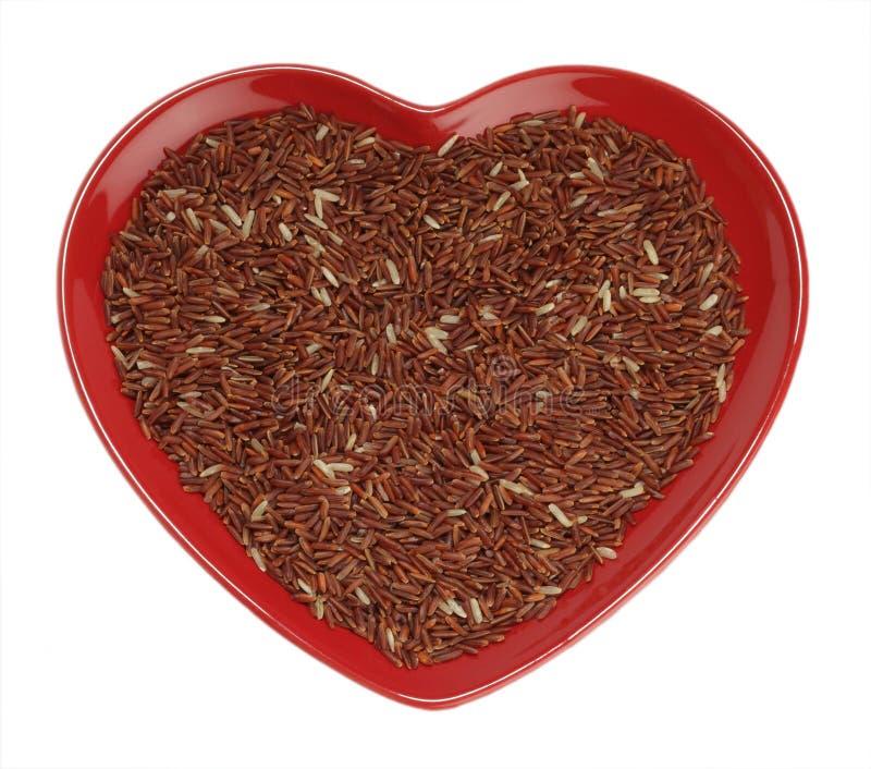 Arroz de grão longo vermelho Himalayan no coração vermelho fotos de stock