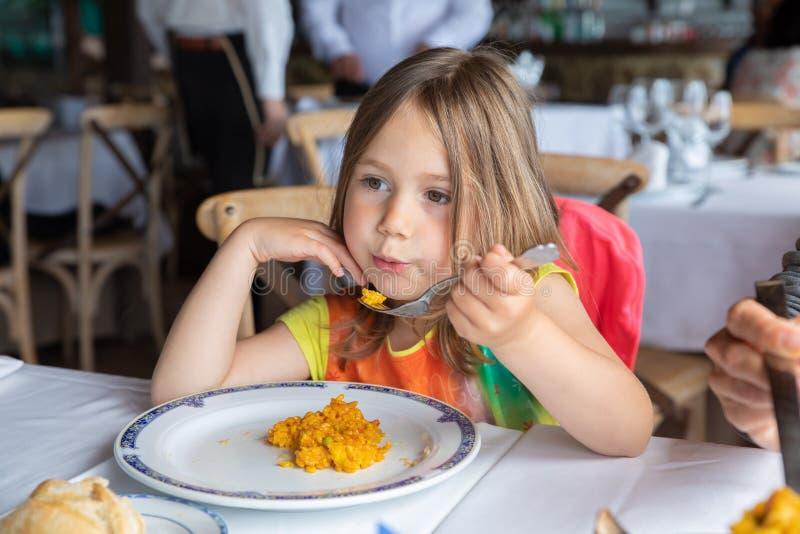Arroz de sopro da menina bonito na forquilha para refrigerar comer o paella no restaura imagens de stock