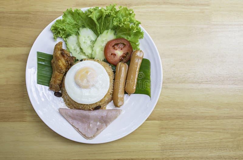 Arroz frito americano com salsicha, presunto, ovos, galinha, tomate, pepino, sobre folhas de banana em prato branco foto de stock