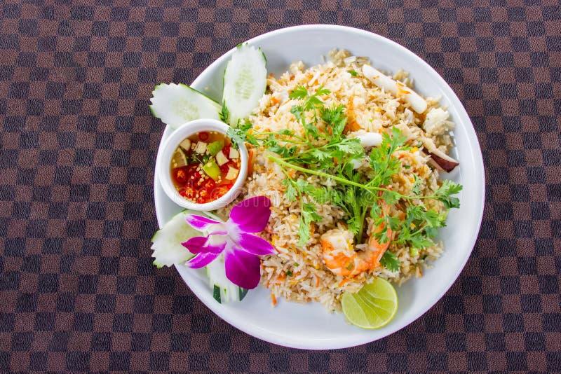 Arroz frito con el camarón en el plato de cerámica blanco adornado con la orquídea y la salsa de inmersión picante caliente puest imagen de archivo