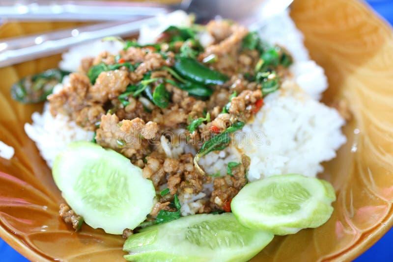 Arroz frito con la albahaca, cerdo picadito con el pepino frito, sabor picante, comida tailandesa foto de archivo