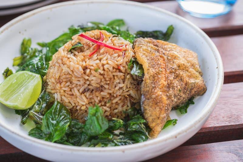 Arroz frito con la albahaca y los pescados fritos curruscantes cortados, comida tailandesa fotos de archivo