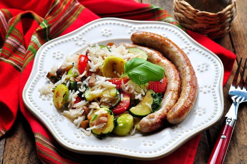 Arroz frito con las salchichas de las coles de Bruselas, de las setas, del calabacín, del ajo, de los tomates de cereza, de la al fotografía de archivo
