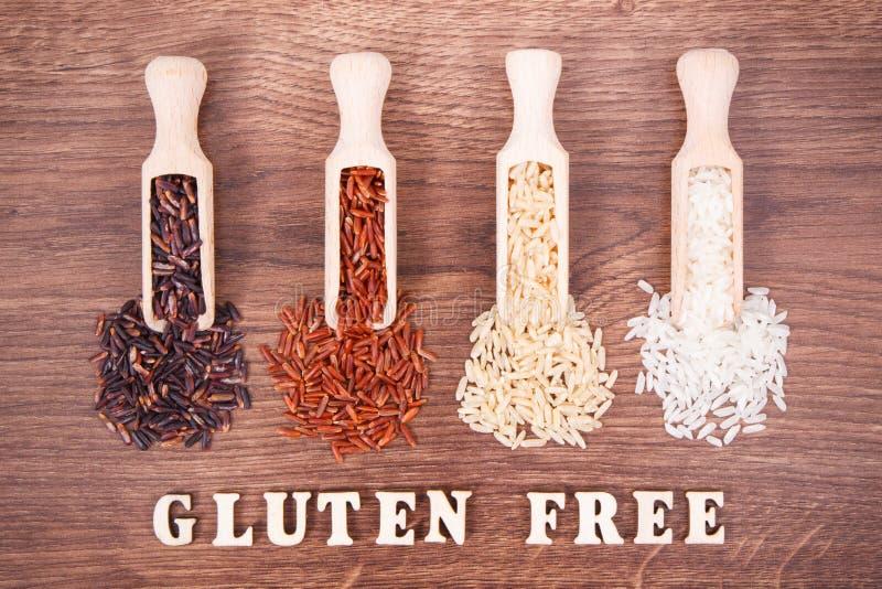 Arroz negro, rojo, marrón y blanco en la cucharada de madera en el tablero rústico, concepto sano de la comida fotos de archivo libres de regalías