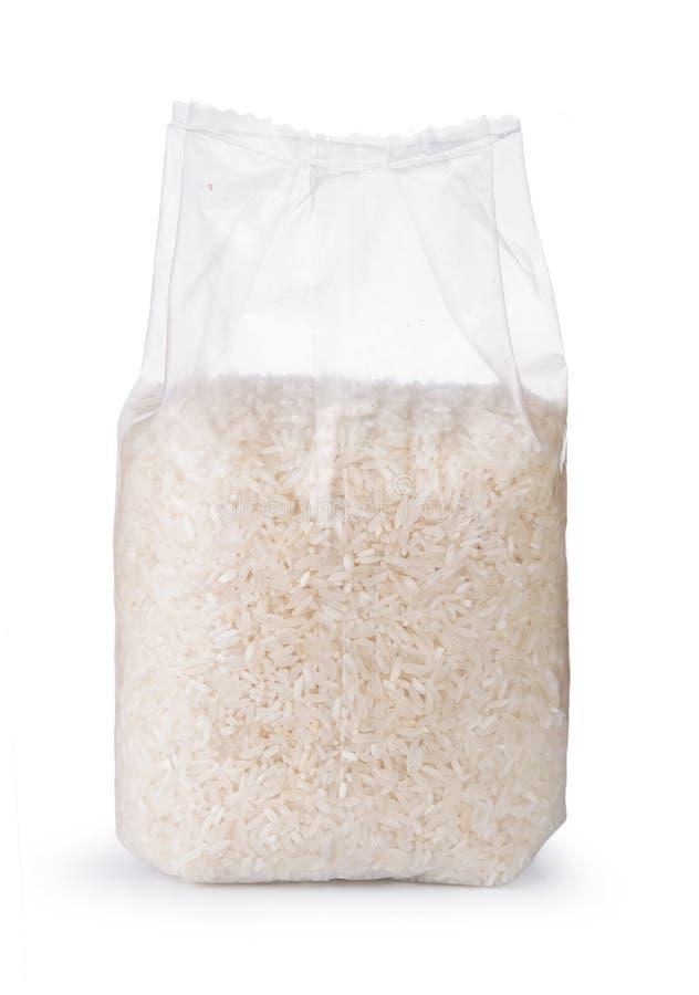 Arroz no saco de plástico transparente no fundo branco imagem de stock