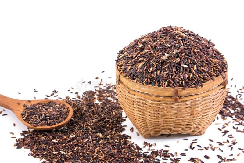Arroz o riceberry moreno en la cesta de bambú y la cuchara de madera aisladas en el fondo blanco fotografía de archivo libre de regalías