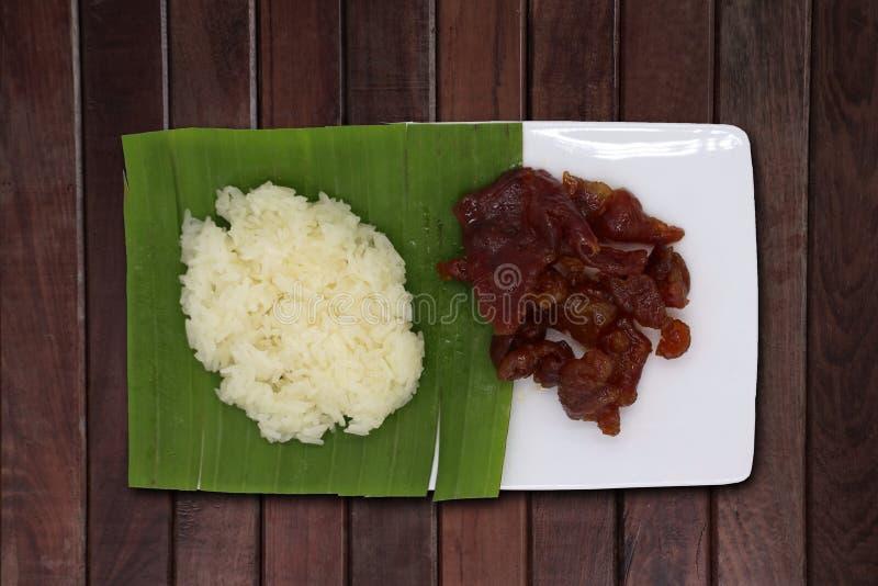 Arroz pegajoso colocado sobre hojas de plátano Servido con cerdo dulce sobre un plato blanco en un suelo de madera foto de archivo