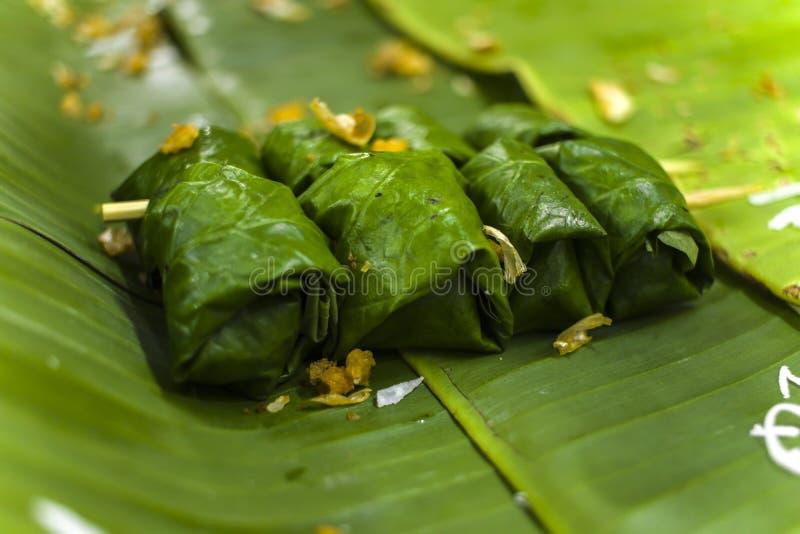 Arroz pegajoso da sobremesa tailandesa, leite de coco e banana envolvidos nas folhas da banana foto de stock