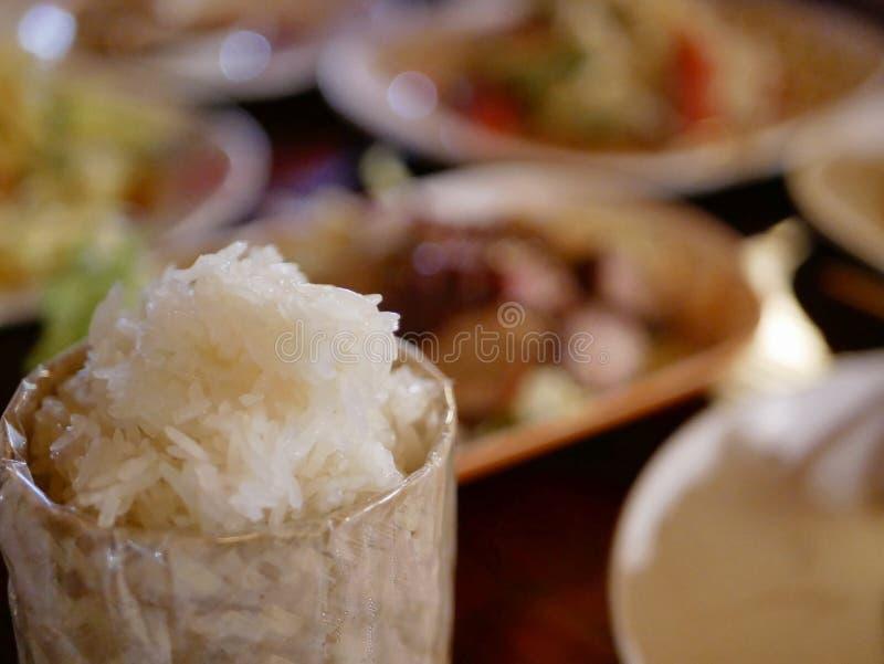 Arroz pegajoso na cesta de bambu do serviço pequeno em um fundo defocused da variedade de alimentos tailandeses foto de stock