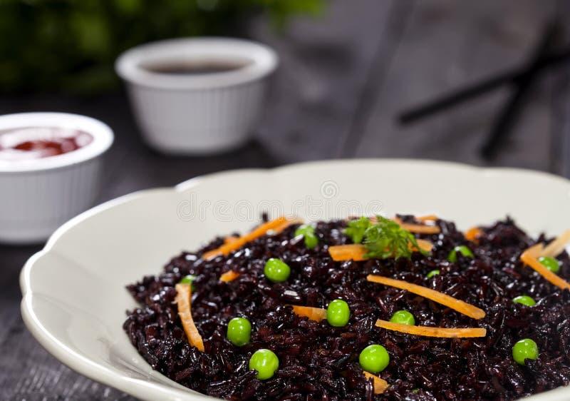 Arroz preto cozinhado com vegetais em uma placa com molhos e hashis no fundo de madeira foto de stock