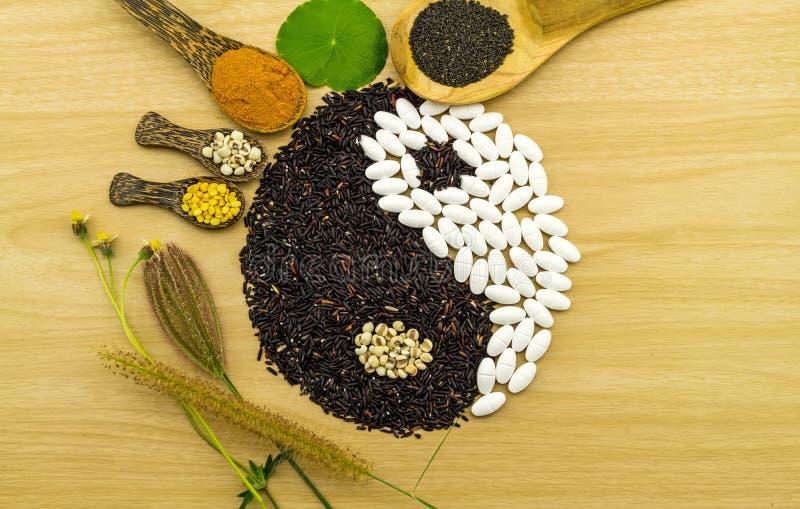 Arroz preto e comprimido branco que formam um símbolo de yang do yin e uma bola de compressão erval dos termas, pó da cúrcuma, pa foto de stock royalty free
