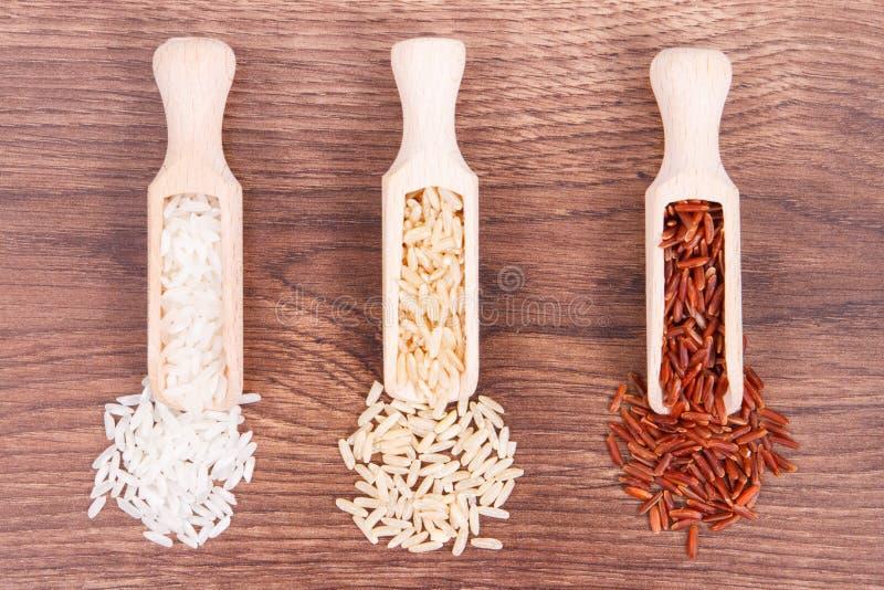 Arroz rojo, marrón y blanco con la cucharada de madera en el tablero rústico, comida sana foto de archivo libre de regalías
