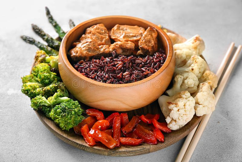 Arroz selvagem fervido saboroso com carne na bacia e nos vegetais na placa foto de stock royalty free