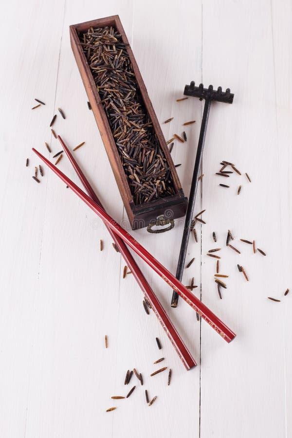 Arroz selvagem preto em uma caixa de madeira com hashis em um fundo de madeira branco foto de stock royalty free