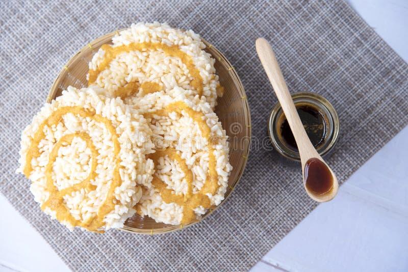 Arroz soplado dulce con caramelo en una botella de cristal en la tabla de madera blanca vieja, postres curruscantes, tailandeses  foto de archivo libre de regalías