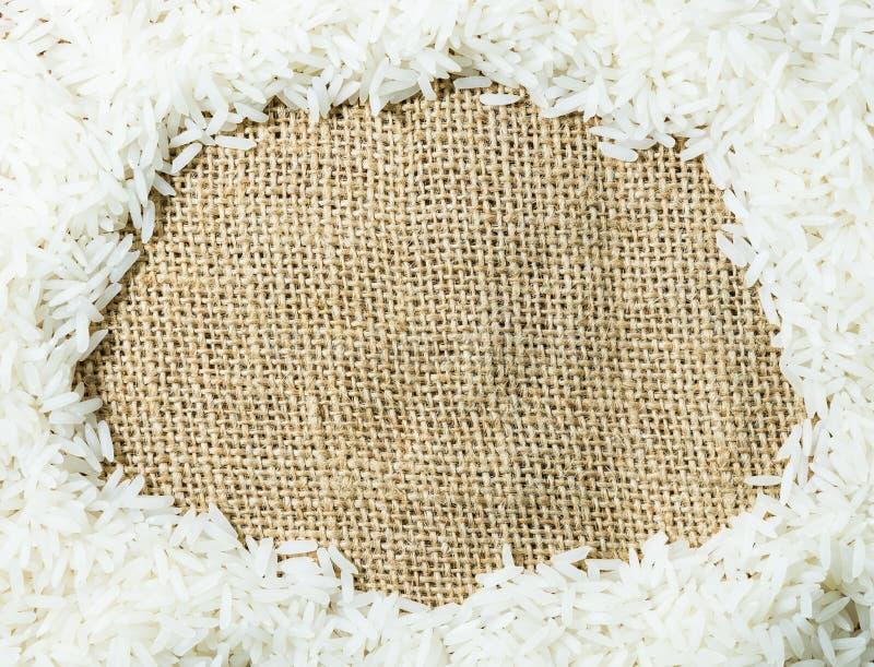 Arroz tailandês cru branco do jasmim na textura de pano de saco do gunny fotos de stock royalty free