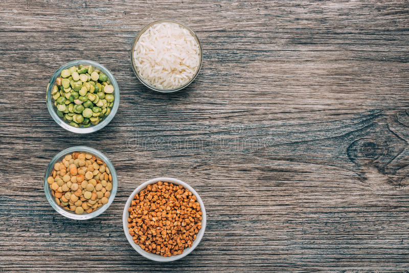 Arroz, trigo mourisco, ervilhas e lentilhas em uns copos pequenos em uma superfície de madeira imagem de stock