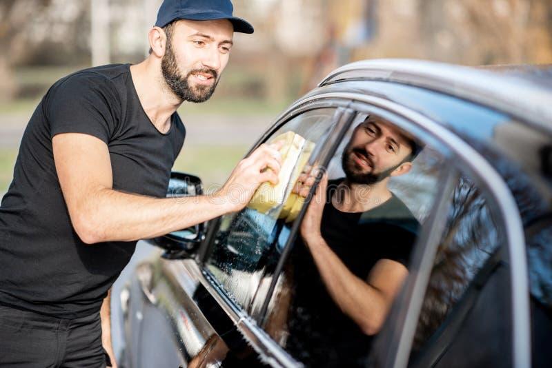 Arruela profissional que limpa a janela de carro fotografia de stock