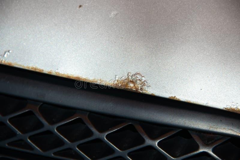 Arrugginisca sul cofano di un'automobile d'argento fotografia stock
