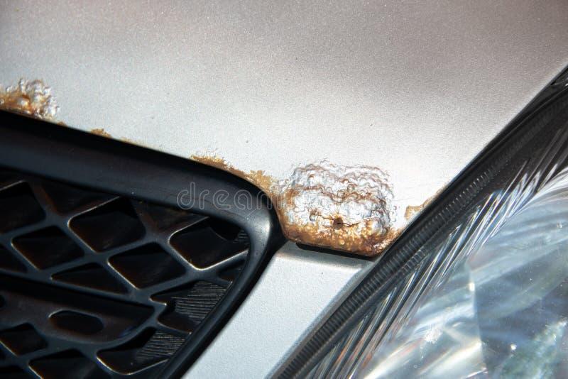Arrugginisca sul cofano di un'automobile d'argento immagini stock