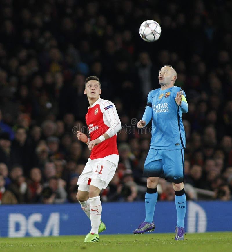 Arsenal FC v FC Barcelona - UEFA Champions League Round of 16: First Leg. LONDON, ENGLAND - FEBRUARY 23: Mesut Ozil of Arsenaland Andres Iniesta of Barcelona royalty free stock image