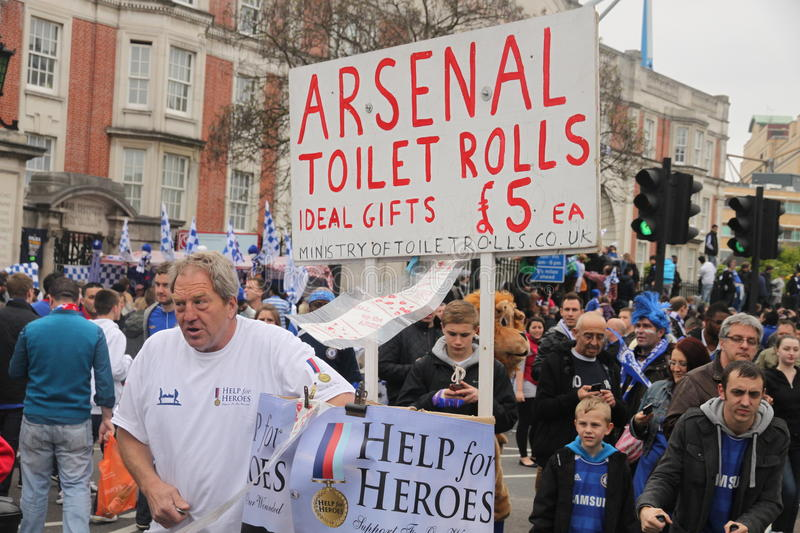 Arsenal toilet rolls. Chelsea football club fan selling arch - rival club Arsenal tiolet rolls during the victory parade after Chelsea have won UEFA Champions royalty free stock images