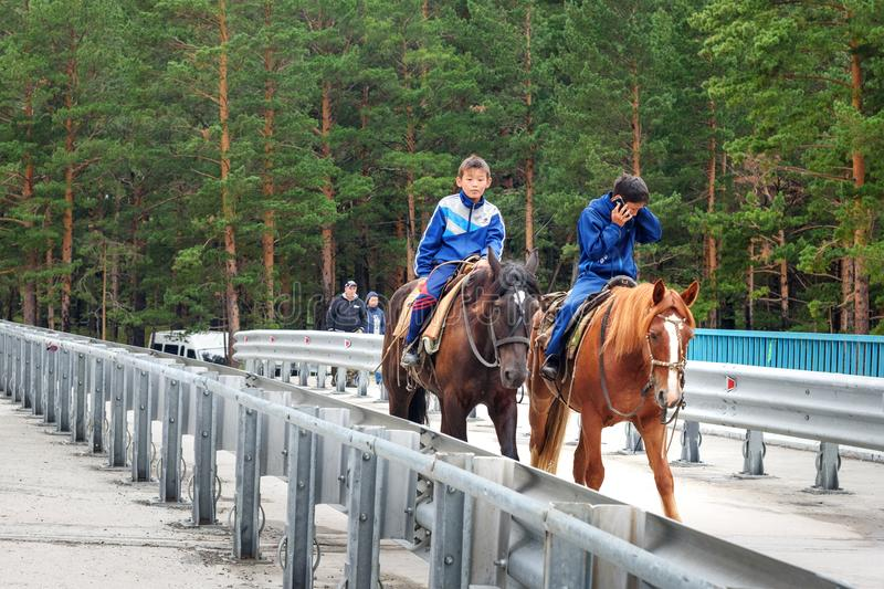 Two Buryat boys ride horses on bridge in Arshan. Russia stock photo