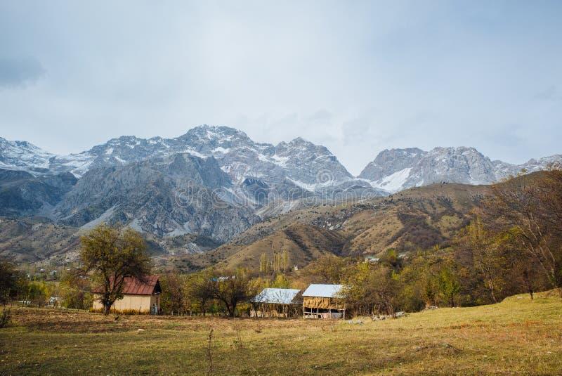 ARSLANBOB, КЫРГЫЗСТАН: Взгляд деревни Arslanbob в южном Кыргызстане, с горами на заднем плане во время осени стоковые фото