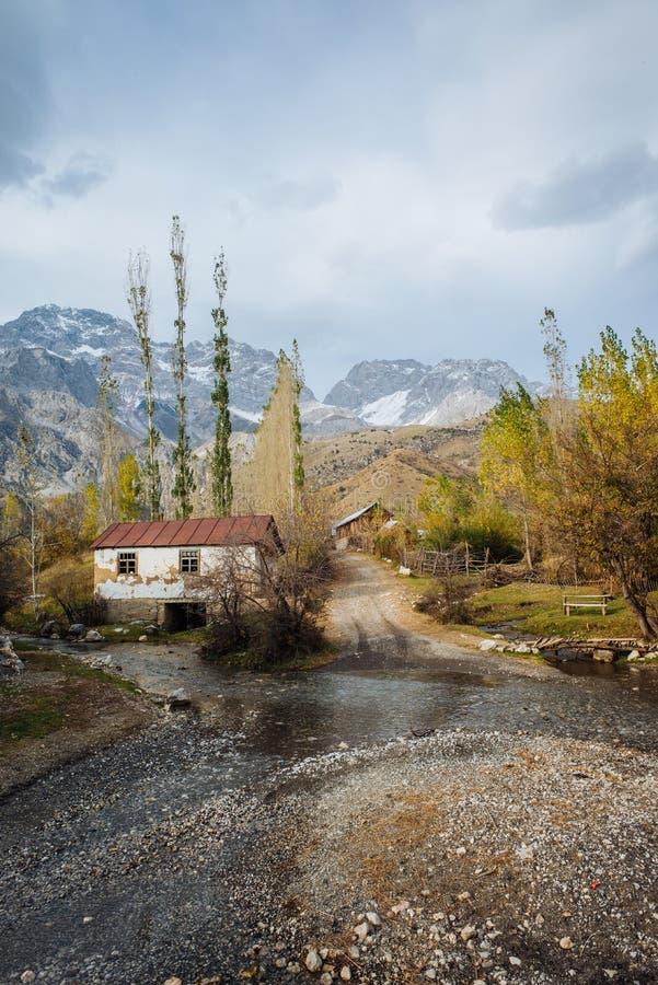 ARSLANBOB, KIRGISTAN: Widok Arslanbob wioska w południowym Kirgistan z górami w tle podczas jesieni, obrazy royalty free