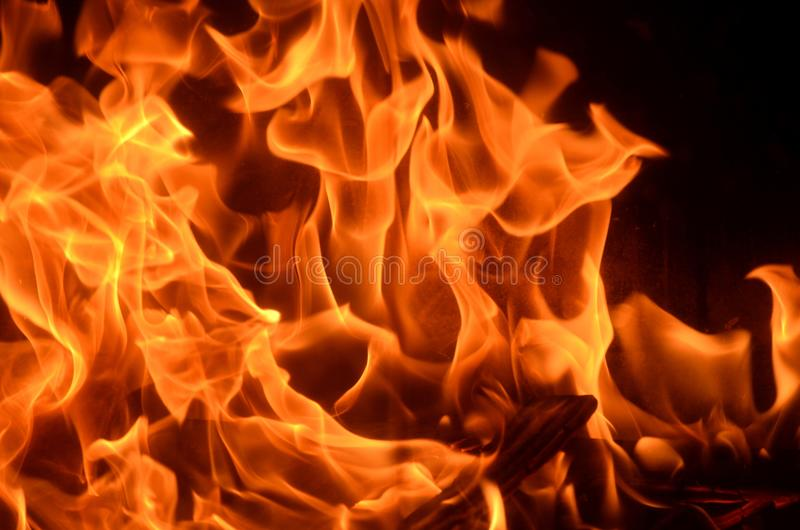 Arson - Closeup of fire burning in a house fire. Danger and fire safety. Wild burning fire and smoldering live coal red, orange and black background stock image