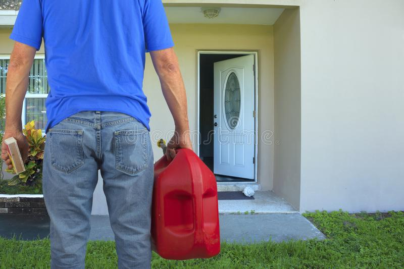 Arsonist man with gasoline can and box of matches preparing to commit arson crime and maliciously burn down a house stock photography