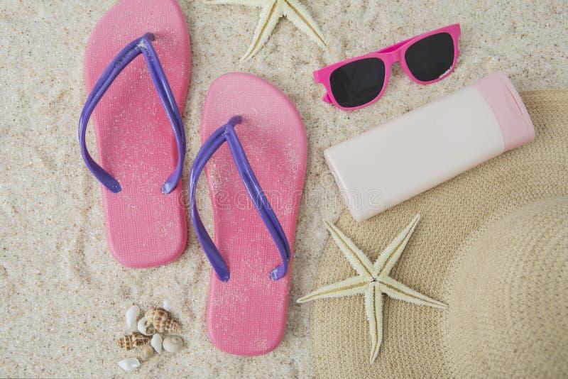 Artículo de la sandalia y de la playa en la arena imagen de archivo