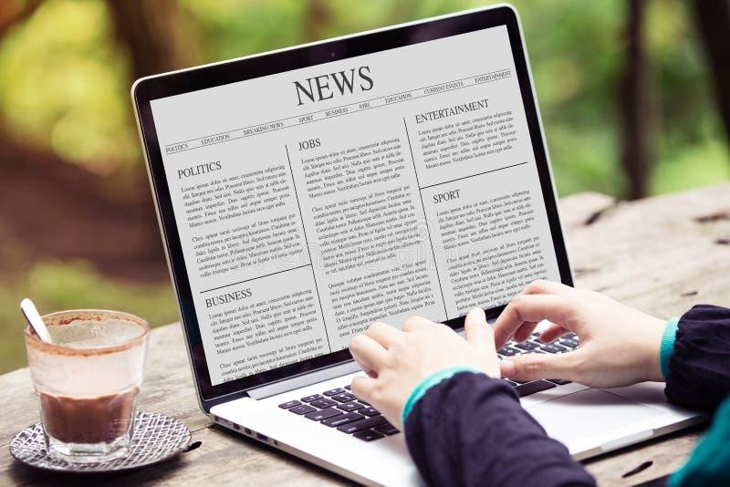 Artículo de noticias de la lectura de la mujer sobre el ordenador portátil/la pantalla de ordenador imagen de archivo libre de regalías