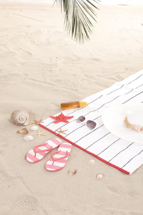 Artículos de la playa en la arena para el verano de la diversión foto de archivo libre de regalías