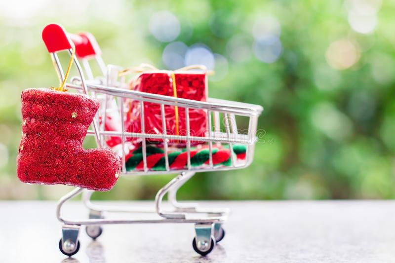 Artículos decorativos de Navidad en mini carro de la compra o carretilla contra b fotografía de archivo libre de regalías