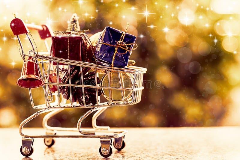 Artículos decorativos de Navidad en mini carro de la compra o carretilla contra b fotos de archivo libres de regalías
